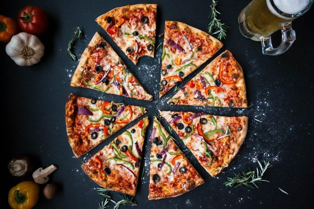 Homepage Oberhausen Pizza. Pizza in acht Teile geteilt und mit diversen Pizza-Zutaten belegt. An der Pizza sind ein Bier, Tomaten und Knoblauch zu sehen.
